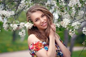 Junge blonde Frau vor Obstblüten
